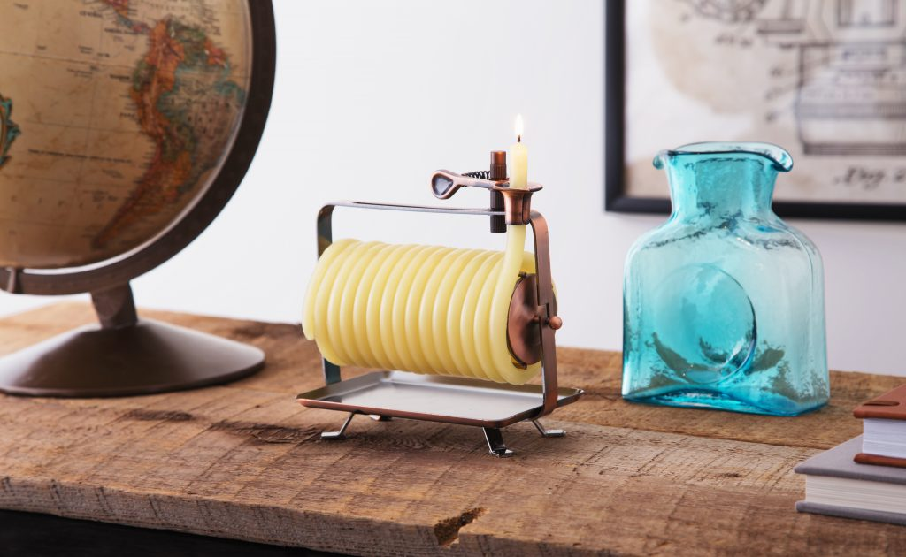 A coiled beeswax candle from Candle By The Hour sits on a desk next to a blue Blenko vase