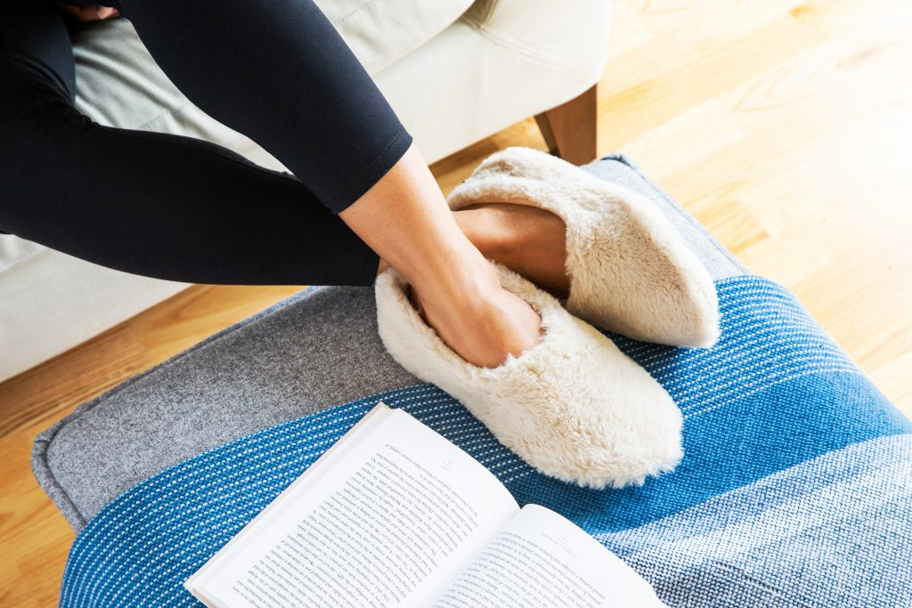 A woman is seen lounging on a couch wearing natural colored Pantuss warming aromatherapy slippers.
