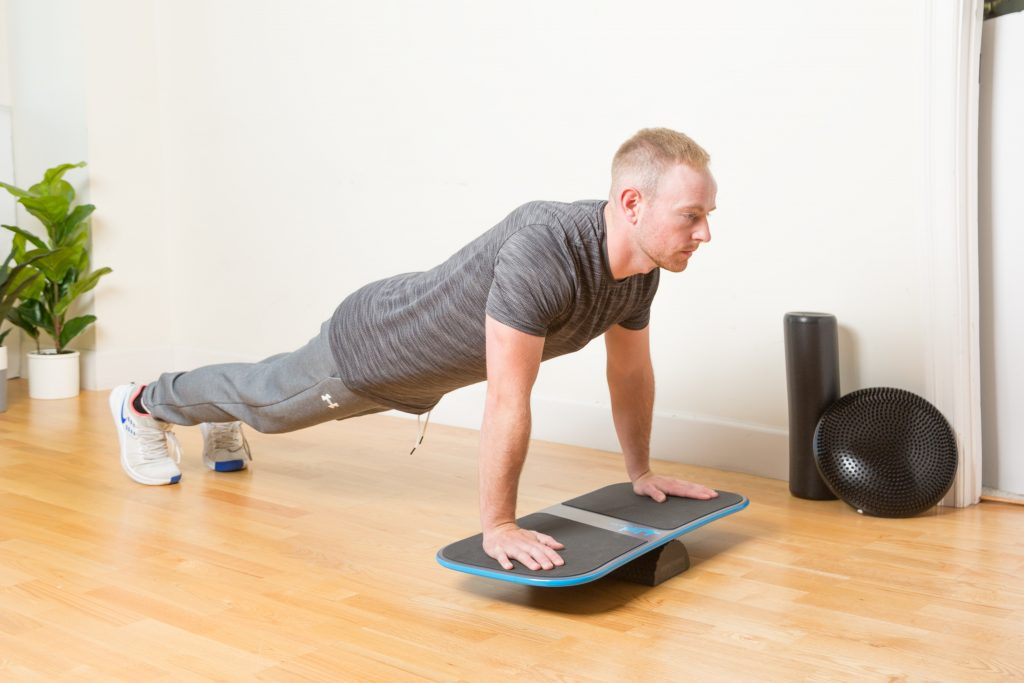 A man is seen planking on a blue Revolution fitness balance board