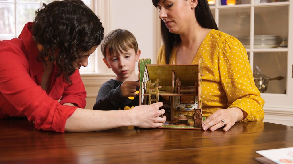 Two women are seen playing with a Storytime Toys storybook house with a young boy