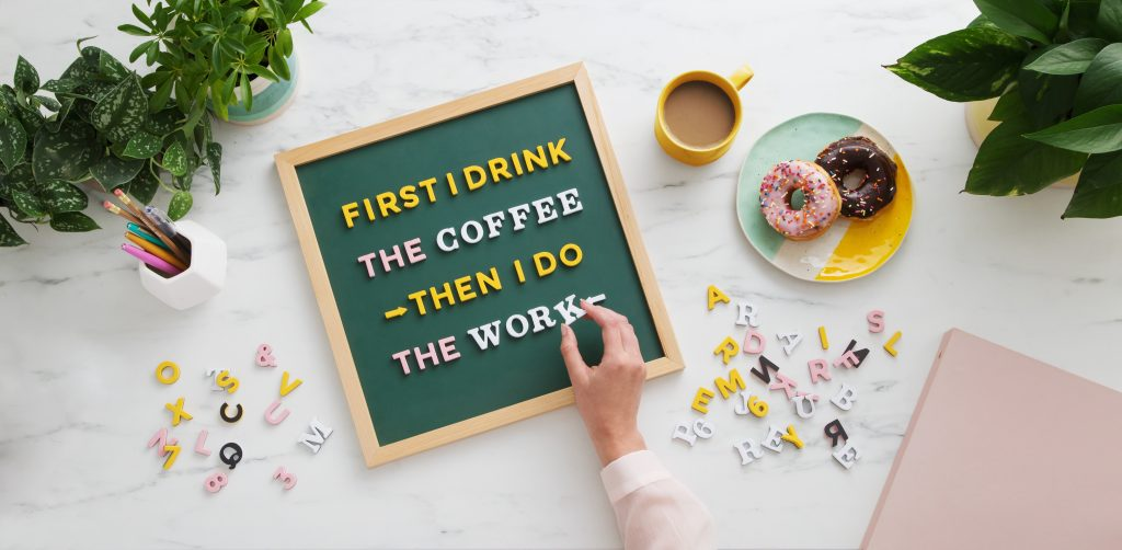 """A woman is seen spelling out """"First I drink the coffee - then I do the work"""" on a Type Set Co message board"""