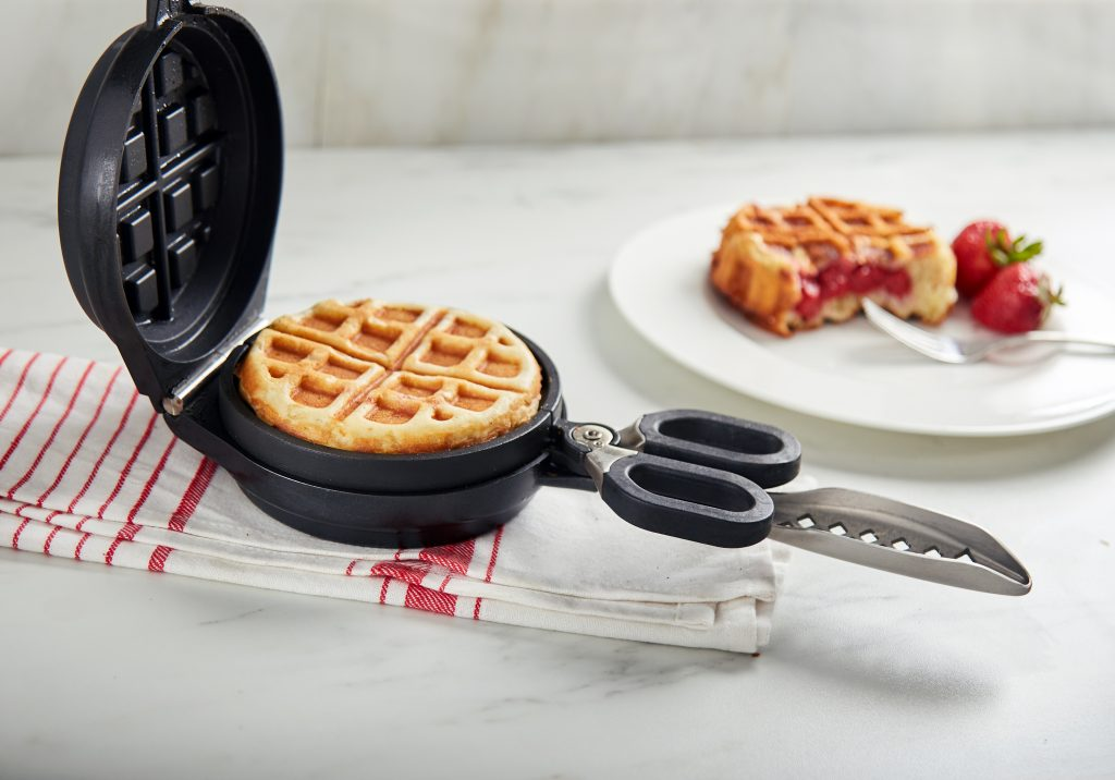 A waffle stuffed with strawberries sits on a plate next to a stuffed waffle maker from Wonderffle, with a fresh waffle in the pan