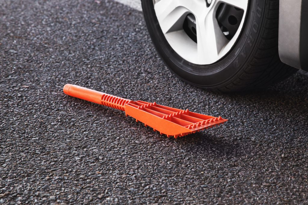 An orange 5-in-1 rescue tool from Spare Me lays on the ground next to a car tire