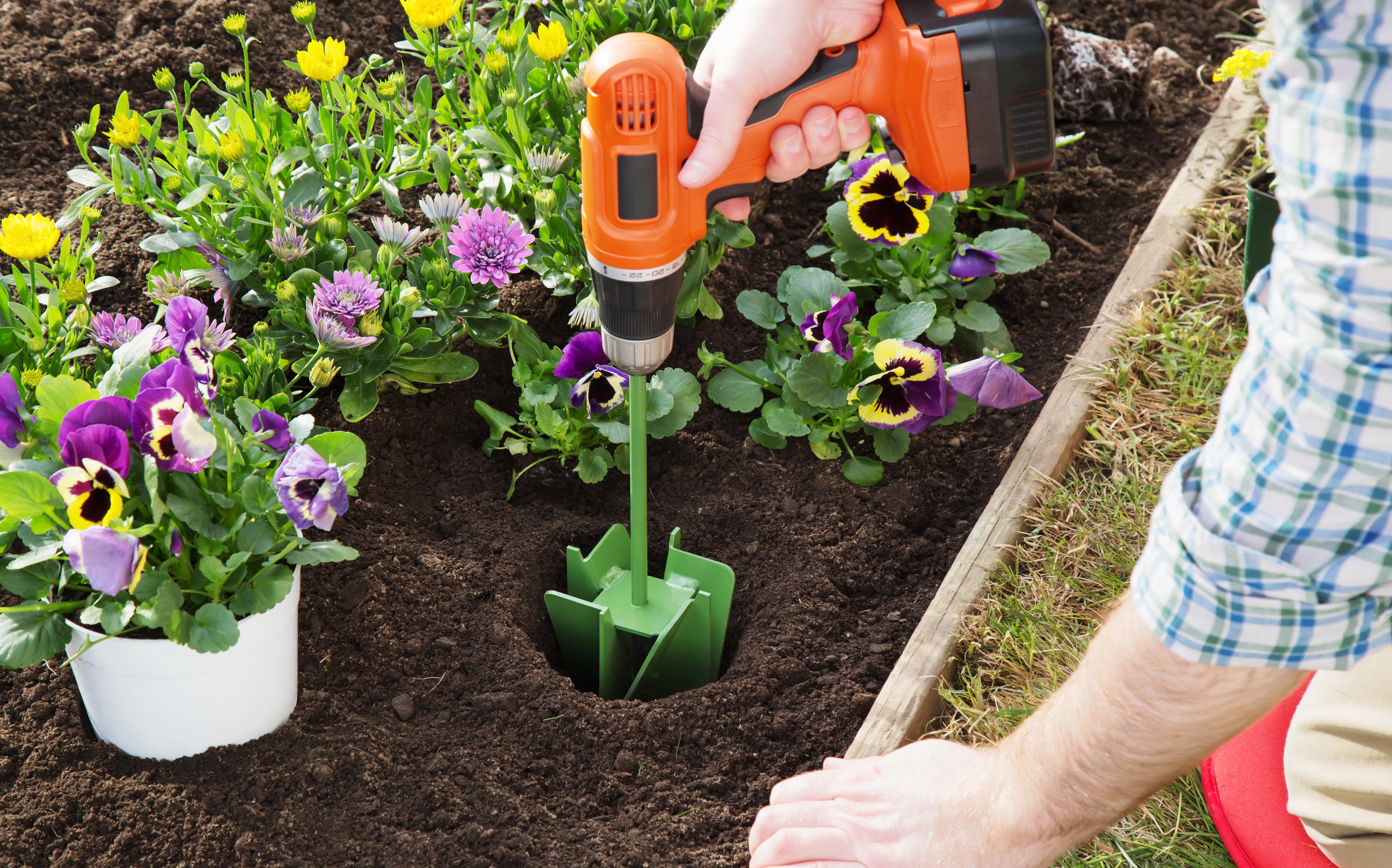 Un hombre hace un hoyo en su jardín usando un bit de excavación MAXBIT
