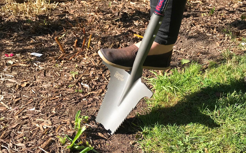 Se ve a una persona aplicando presión de pie a un cortacésped Radius Garden para excavar el suelo