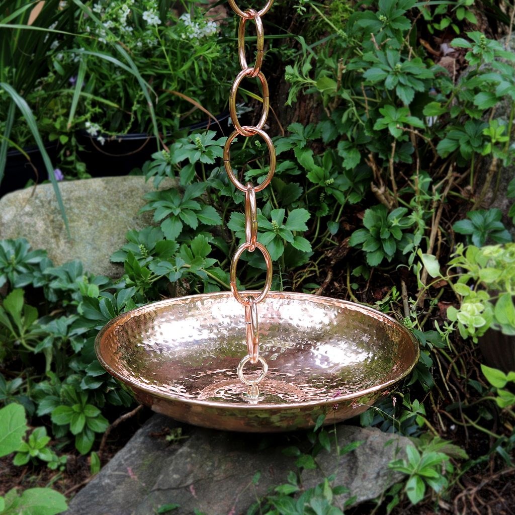 Good Directions copper rain chain basin, outside in the garden