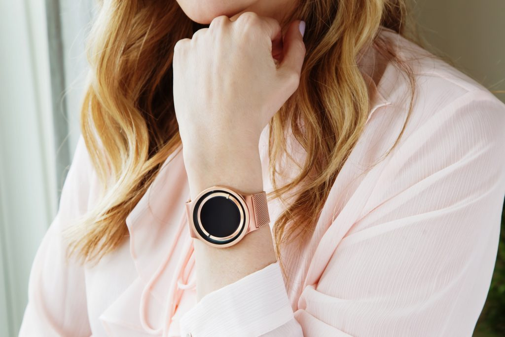 A woman is seen wearing a rose gold ZIIIRO Eclipse bold minimalist watch