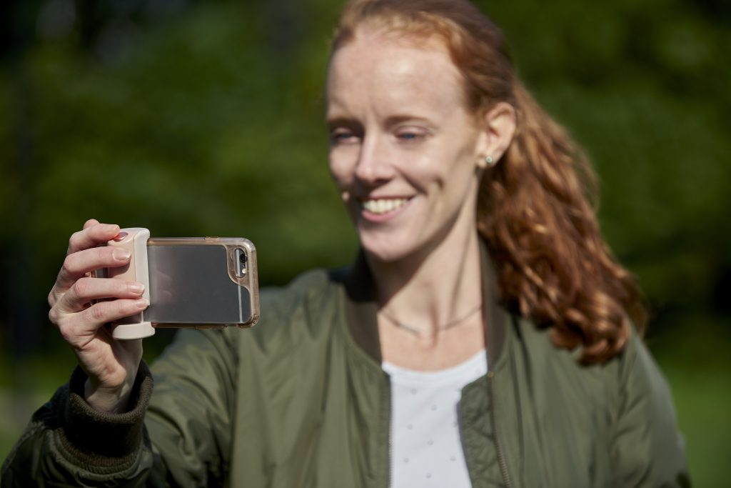Woman takes selfie using Shuttergrip's bluetooth remote shutter