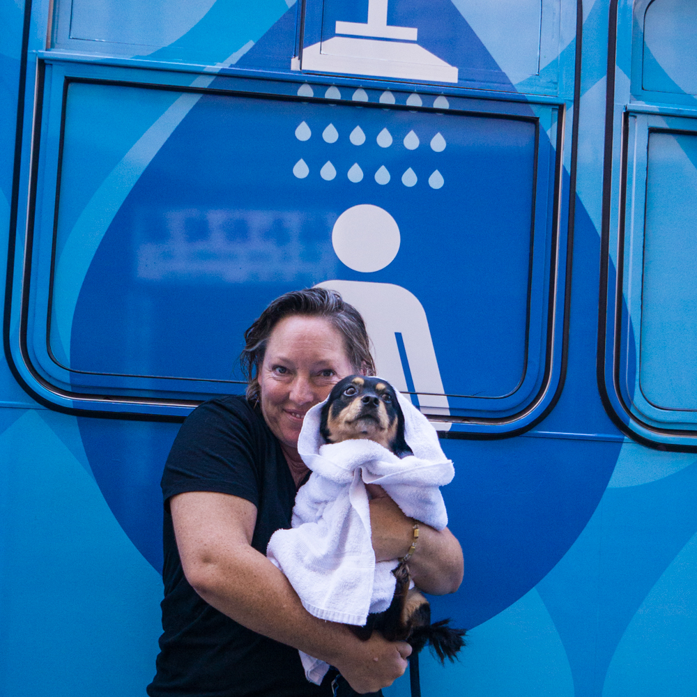 Happy female patron of Lava Mae poses with her freshly showered dog
