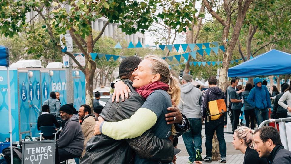 Lava Mae team member hugs grateful man