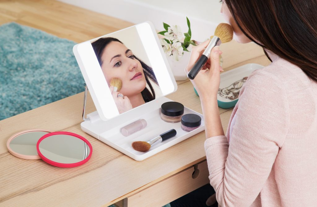 A woman brushes on makeup in front of of Spotlight HD's bright daylight LED makeup mirror