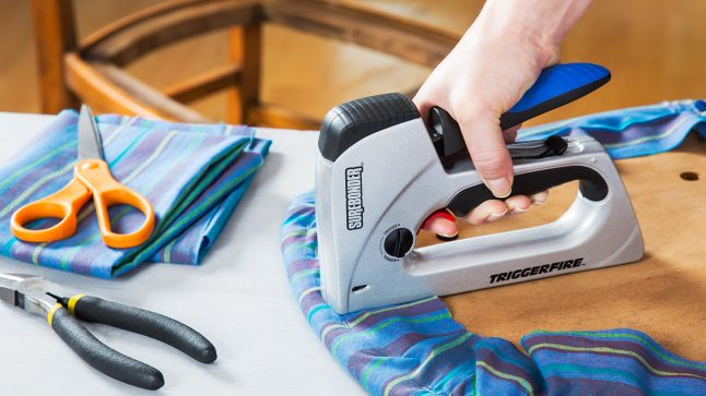 A TriggerFire kickback-free staple gun is seen being used to upholster furniture