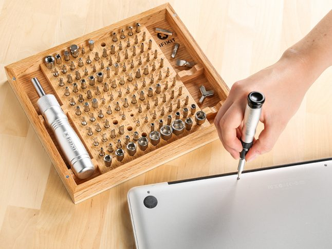 A person uses an iFixIt universal bit kit to fix a laptop