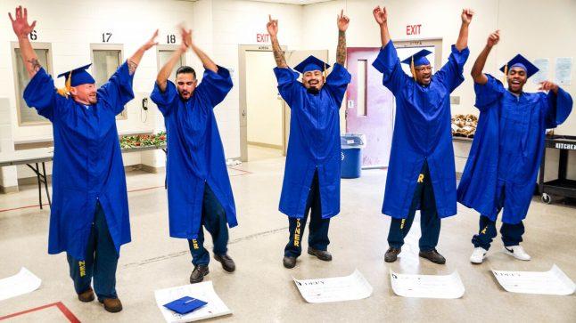 5 men in blue graduation cpas & gowns are seen celebrating having graduated from Defy Ventures' entrepreneurship training