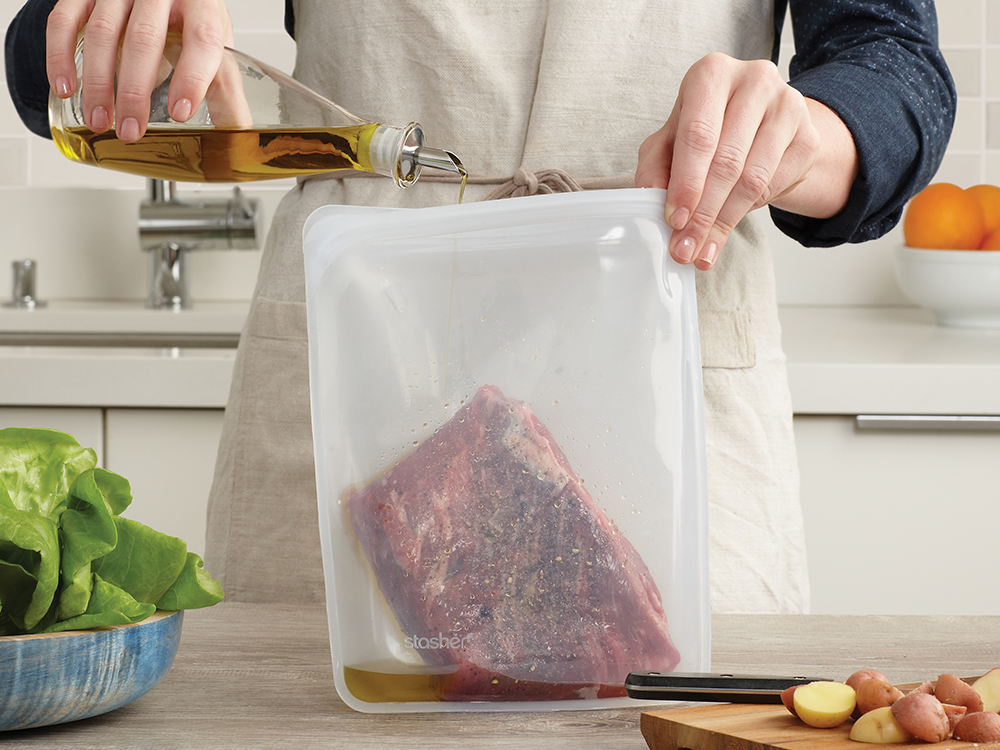 A cook marinates steak in a half gallon silicone storage bag from Stashers