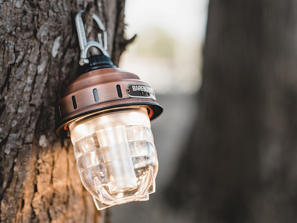 A beacon lantern from Barebones Living hangs on a tree in the woods