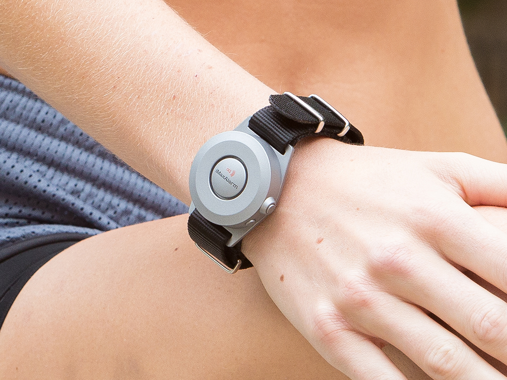 A person wears a black & silver wearable person safety alarm on their wrist