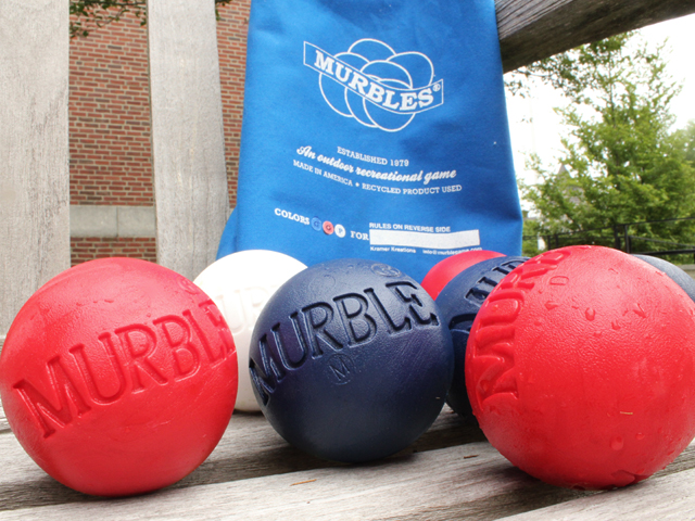 Red & blue Murbles outdoor bocce game sit on a deck