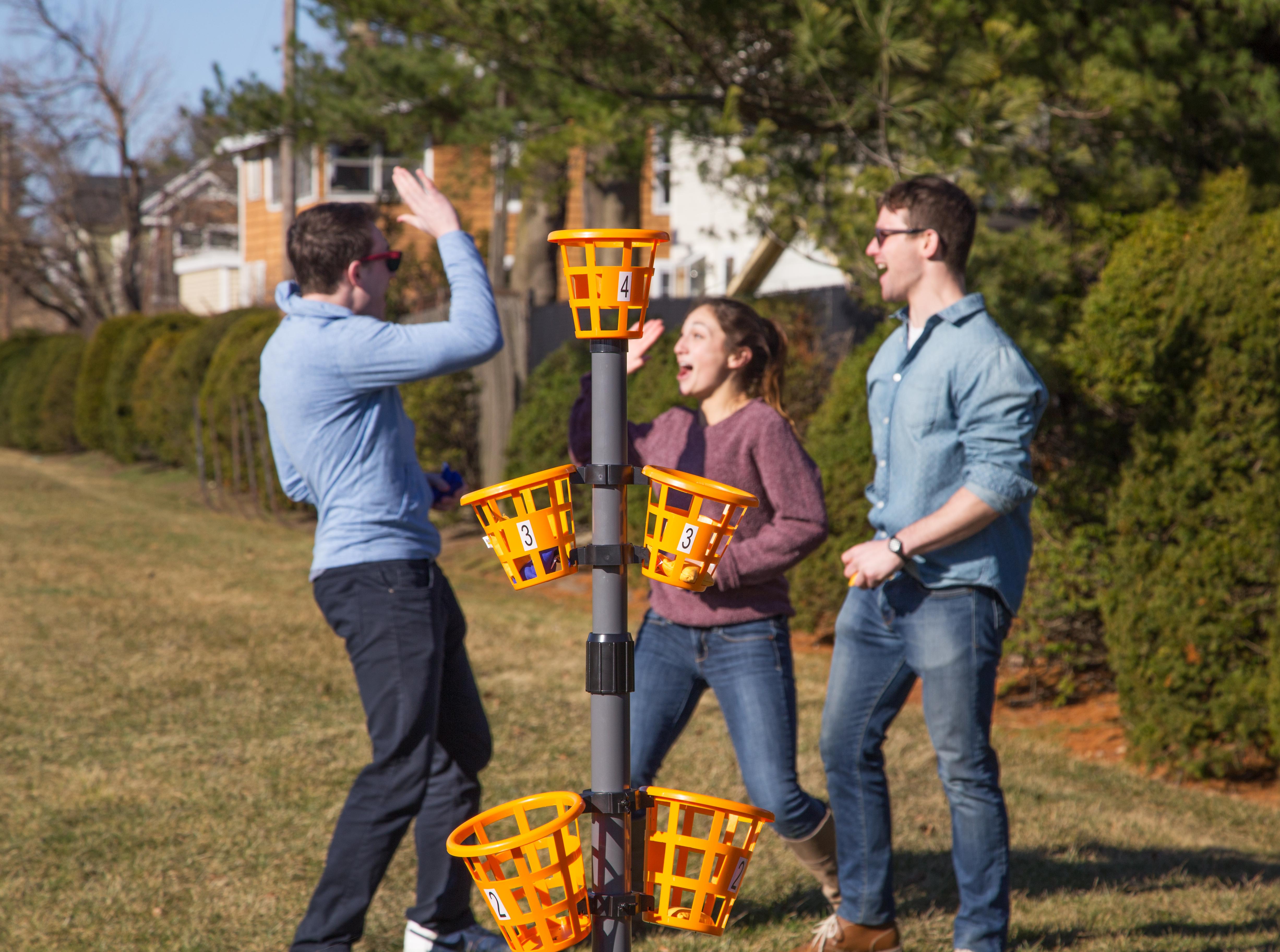 Three people play bean bag basket game in a yard.