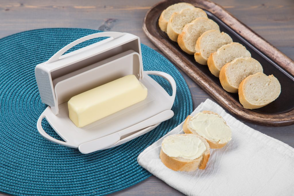 A cream-colored Butterie holds a stick of softened butter next to a sliced baguette
