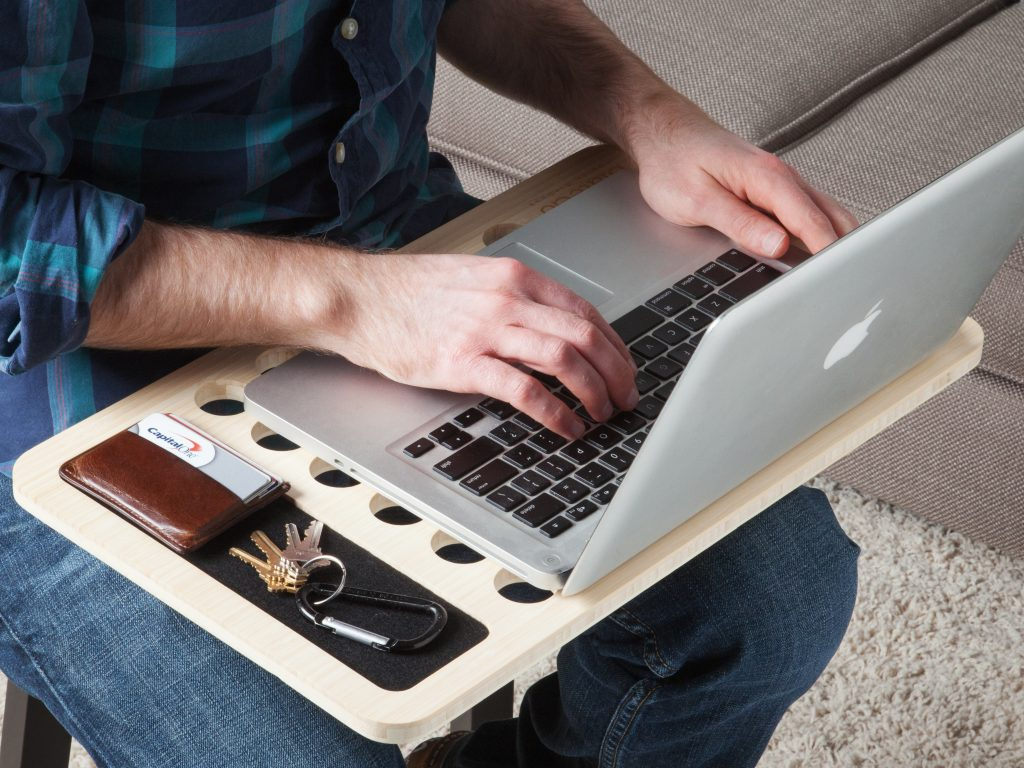 A man sits working on a laptop in his lap, organized with an iSkelter mobile lap desk
