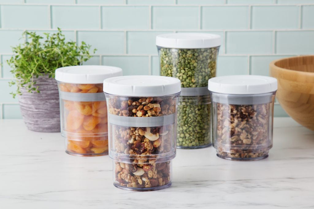 Four collapsible storage containers from Botto sit on a kitchen counter, filled with nuts, dried fruit and dried peas