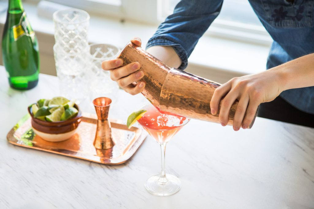 A man is seen pouring a cocktail into a martini glass from a copper bar set from Sertodo