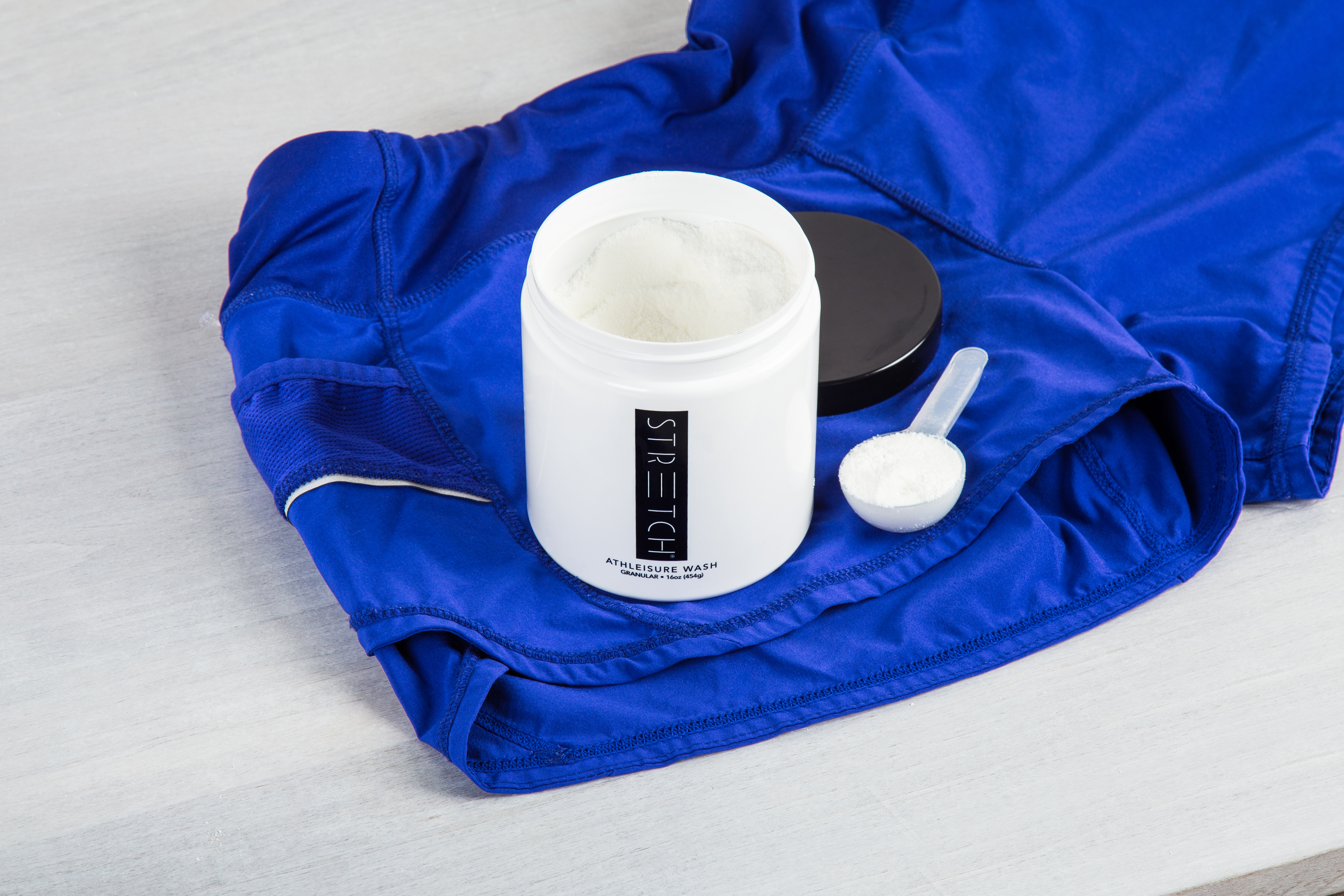 A jar of STRETCH activewear laundry detergent sits atop blue workout gear