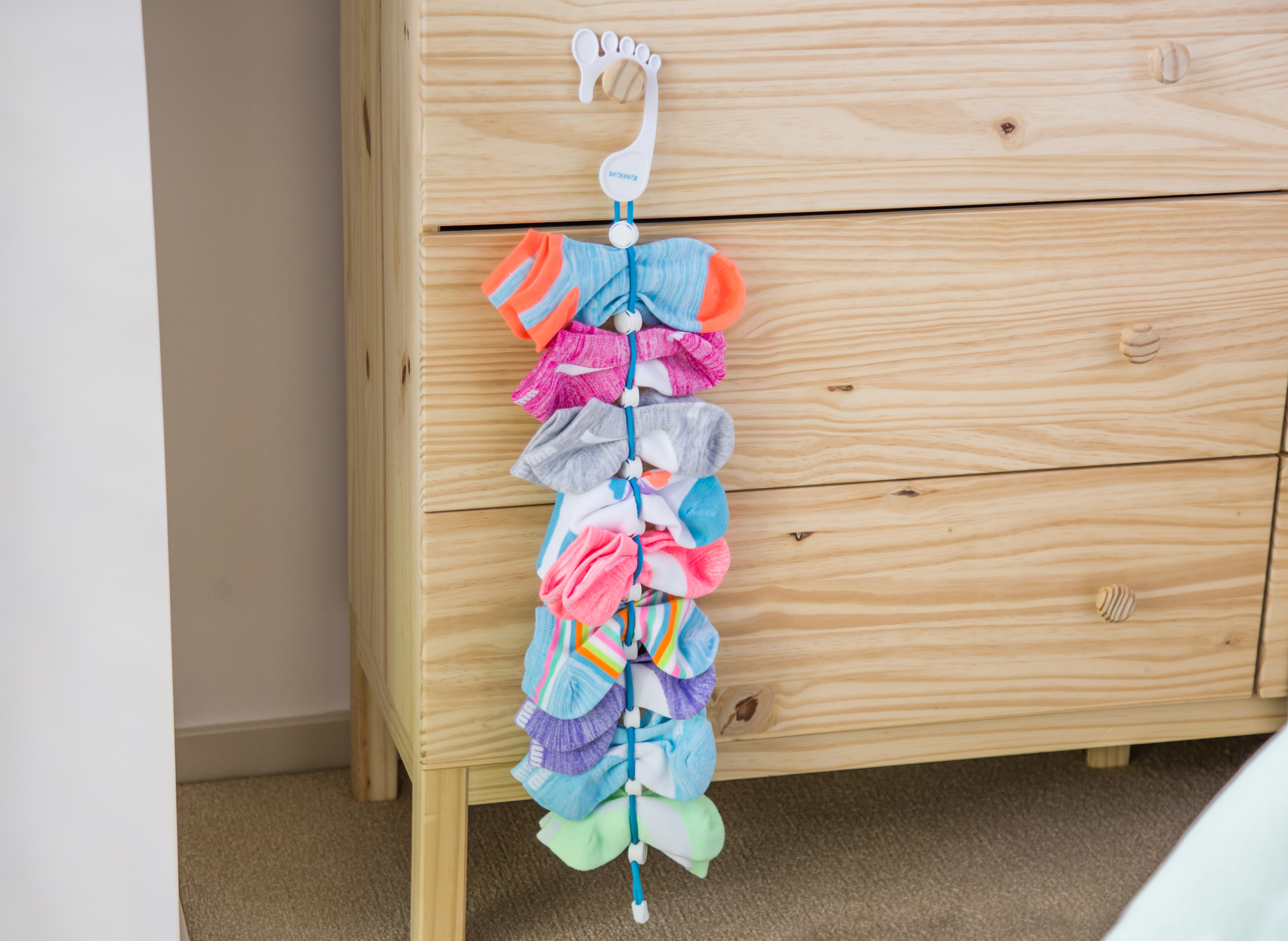multicolored socks are seen hanging in a SockDock