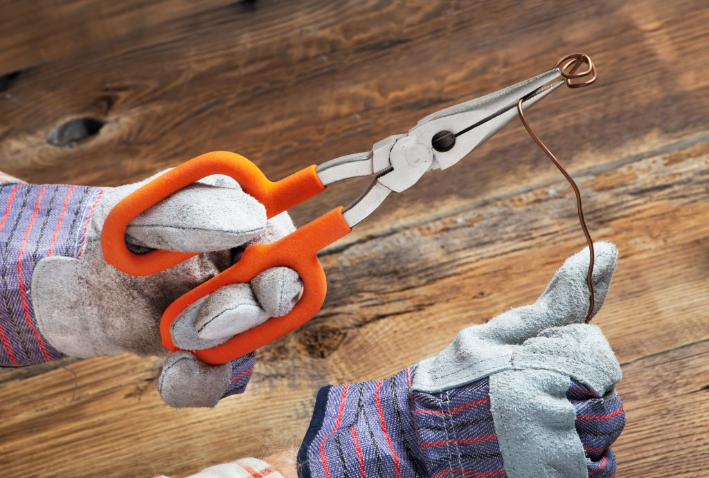 A person with work gloves uses Handle Rite's ergonomic loop handle pliers to bend metal wire