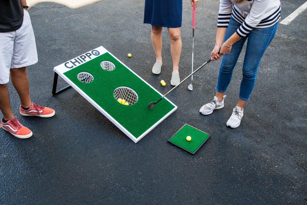 Three people are seen playing Chippo Golf in a driveway