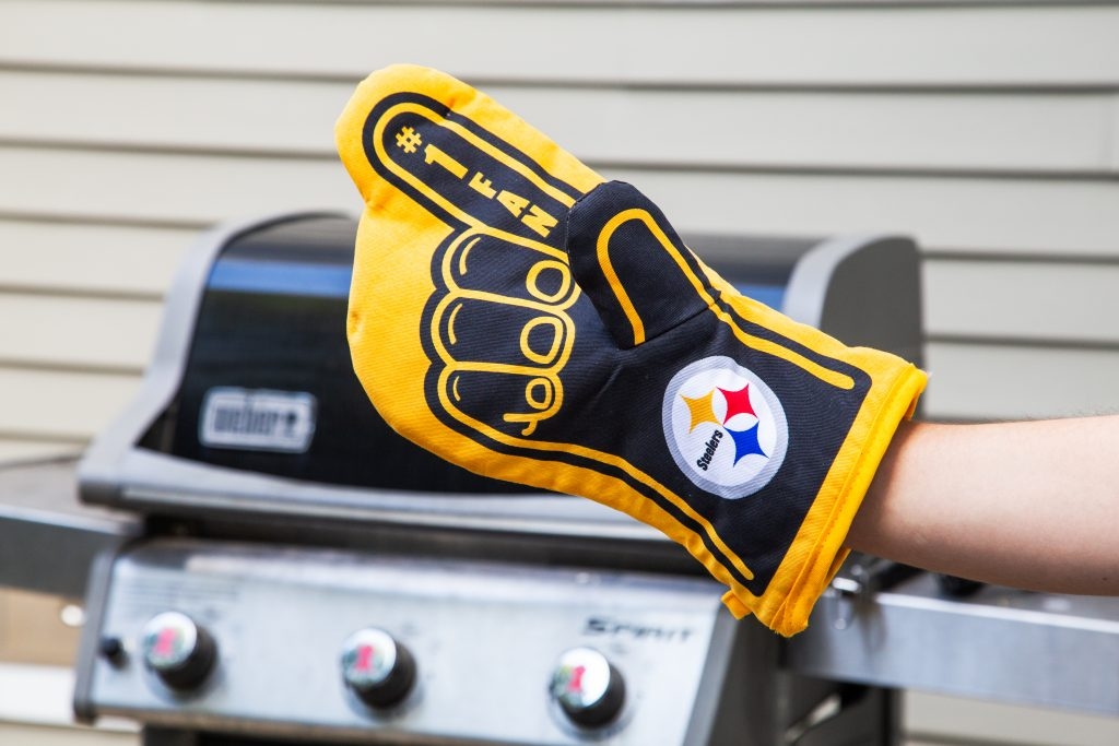 A Steelers fan reps his team at the grill with Sportula's #1 Oven Mitt
