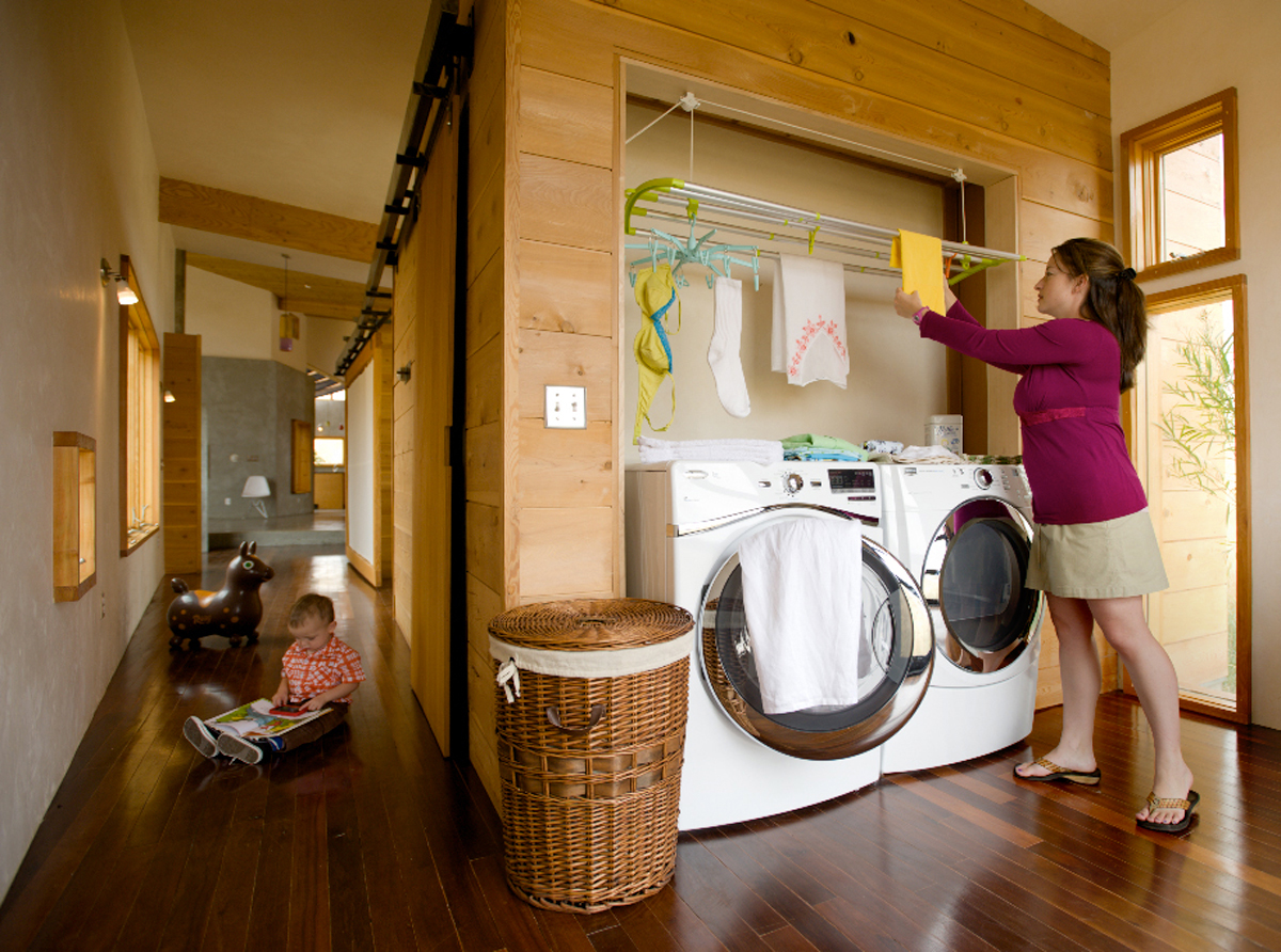 A woman uses LOFT;s hanging laundry rack to hang wet clothes in her laundry closet