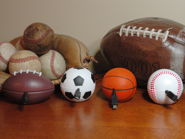 Football, soccer, basketball & baseball Cord Buddies sit on a table with a football and a catcher's mitt