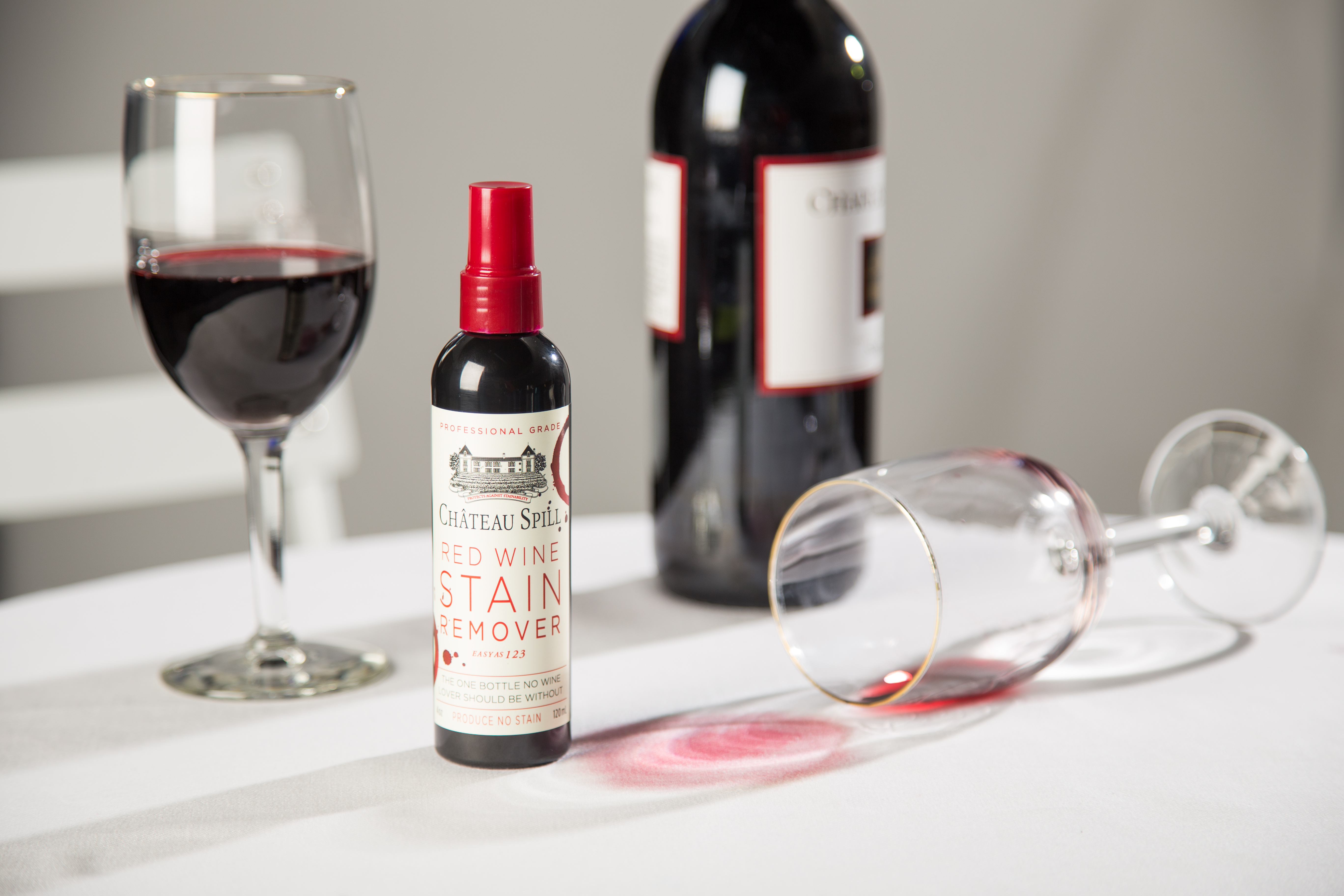 A bottle of Chateau Spill Red Wine Stain Remover sits on a tablecloth stained with red wine