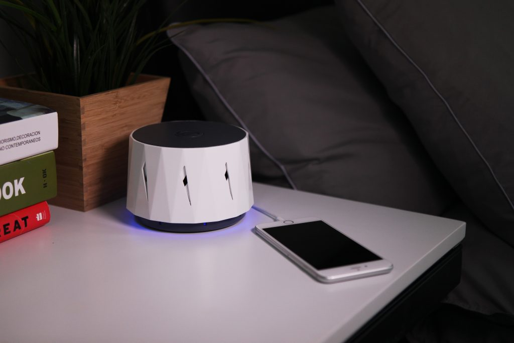 A DOZZI white noise machine sits on a bedside table next to a smartphone