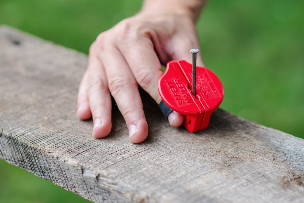 A man safely nails a nail into a wooden plank with SafetyNailer's magnetic nail holder
