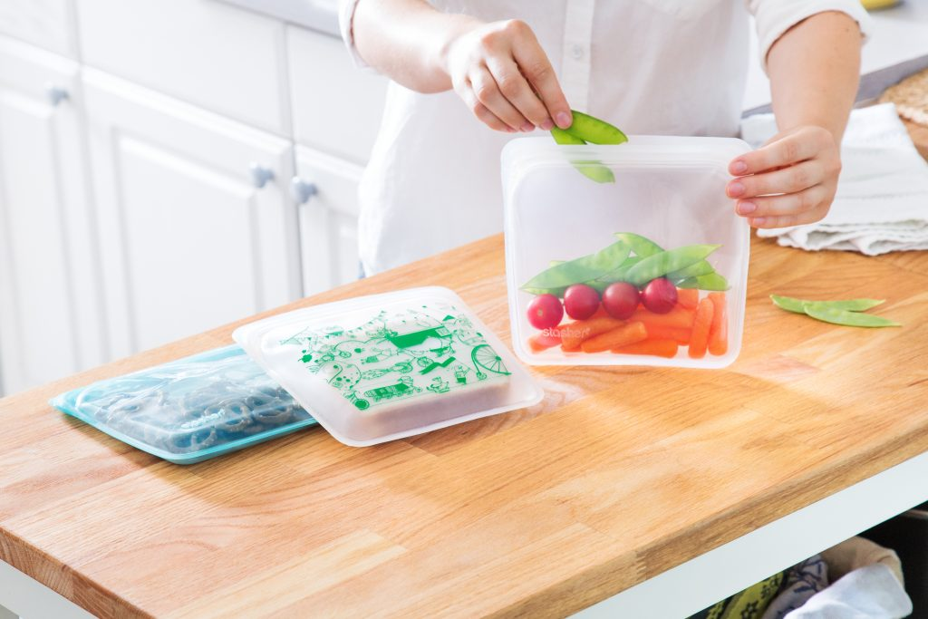 A woman places fresh veggies into Stashers reusable silicone bags