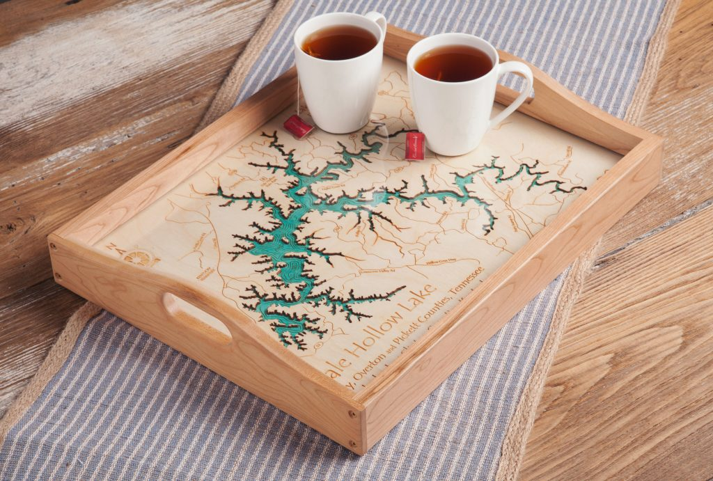 Two cups of tea sit on a wooden tray that is laser-engraved with the map of Eagle Hollow Lake