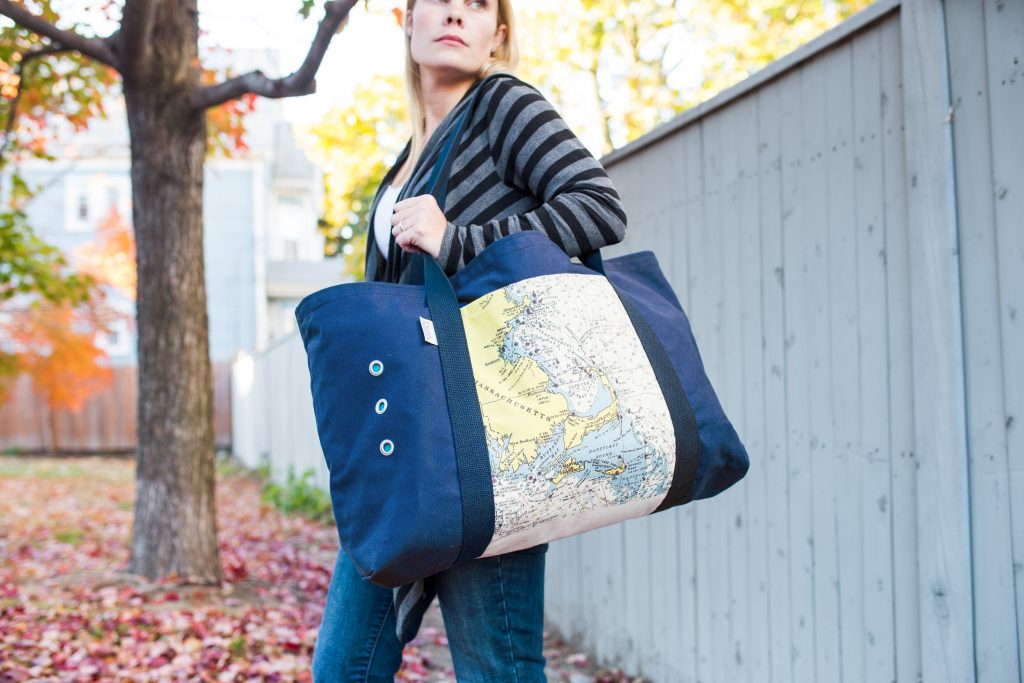 A woman walks carrying a large navy custom nautical beach tote from Not For Navigation
