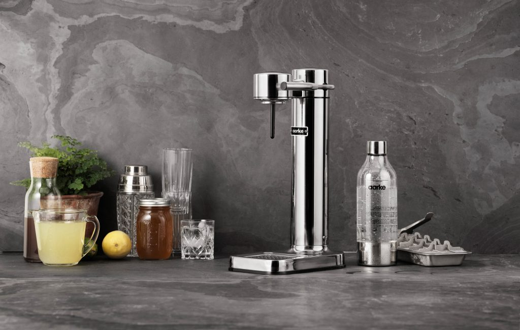 A sleek, stainless steel water carbonator from Aarke sits on a counter alongside other kitchen items