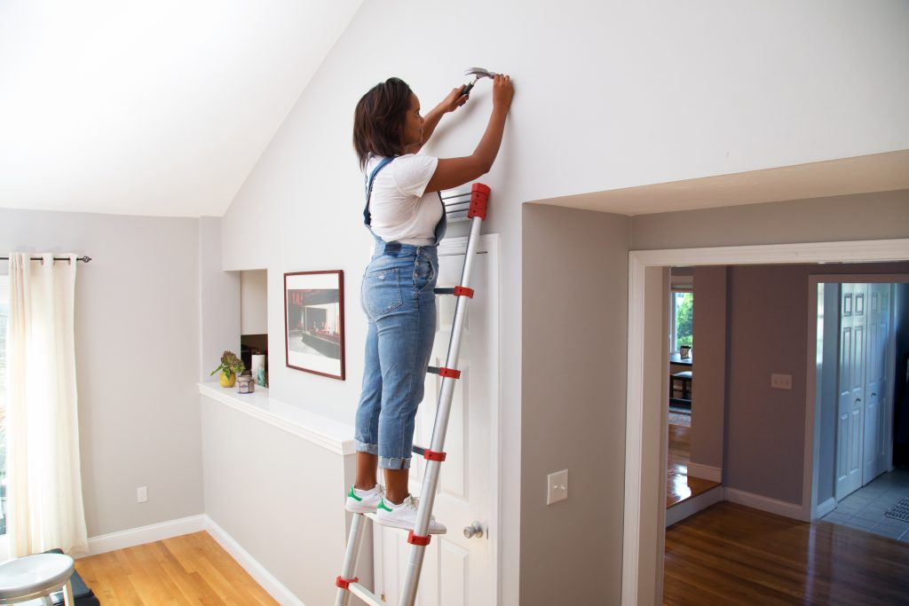 A woman nails a nail high into a wall with Xtend+Climb's extendable ladder