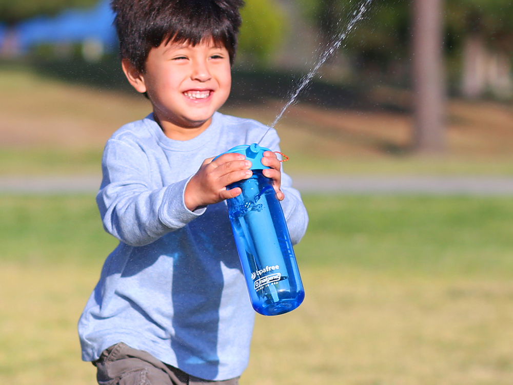A child is seen squirting water from  a blue Aquabot sprayer bottle