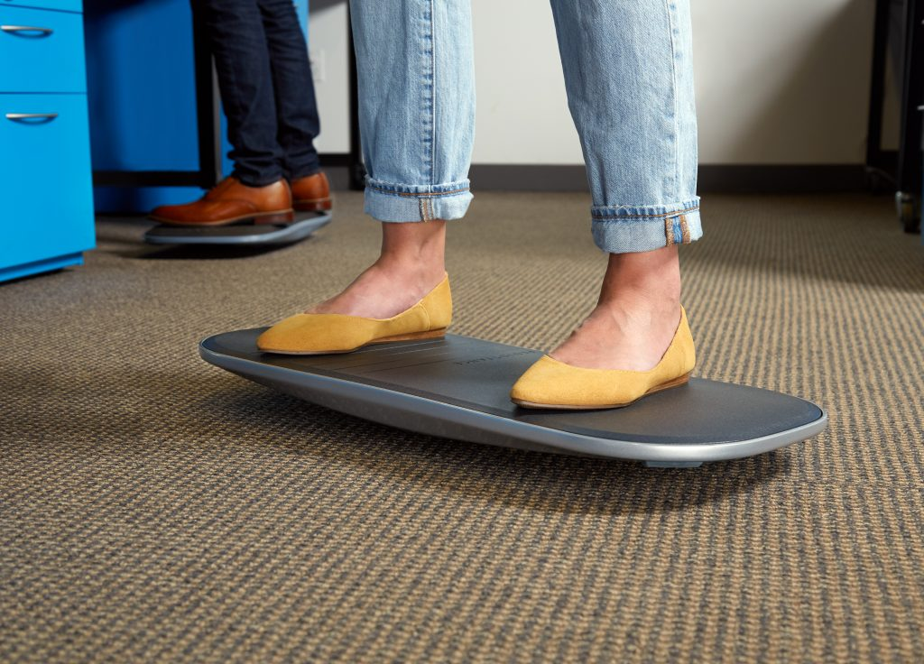 Men & women are seen standing on balance boards while working in an office