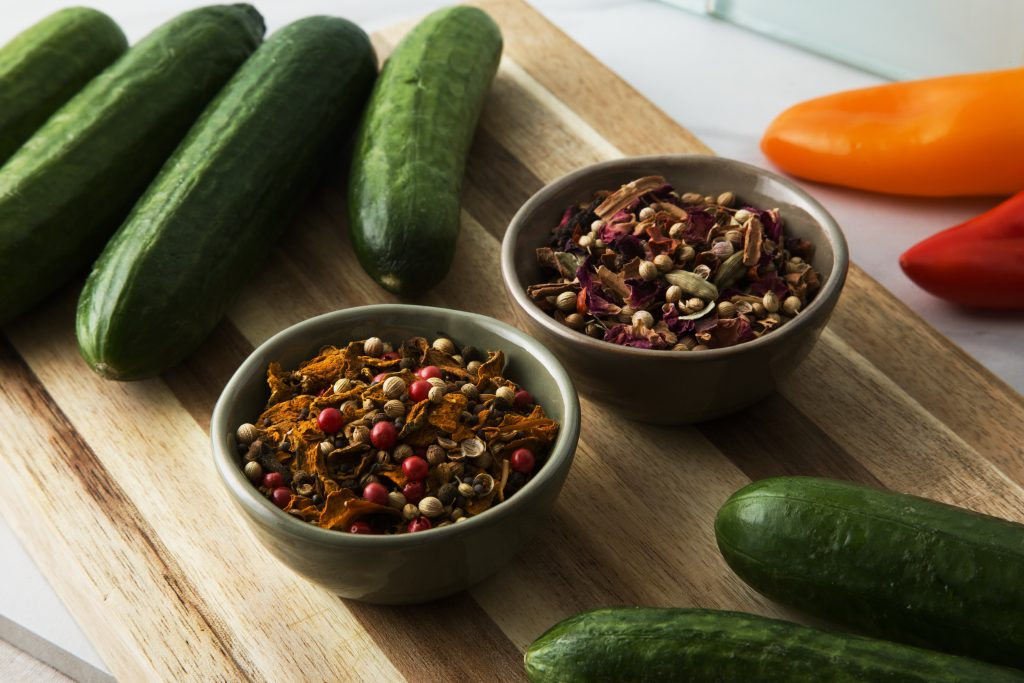 Bowls of Curio Spice Co's pickling spice blend sit on a cutting board with fresh pickling cucumbers