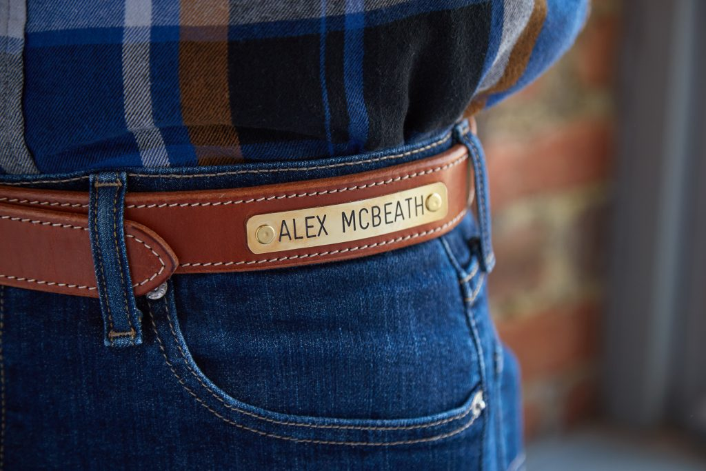 The name 'Alex McBeath' is seen engraved on a Clayton & Crume leather belt with bridle nameplate