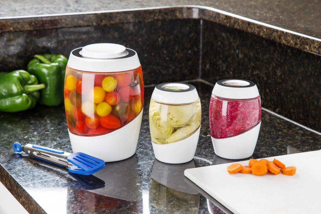 Three Mortier Pilon crocks of various veggies sit on a counter as they ferment
