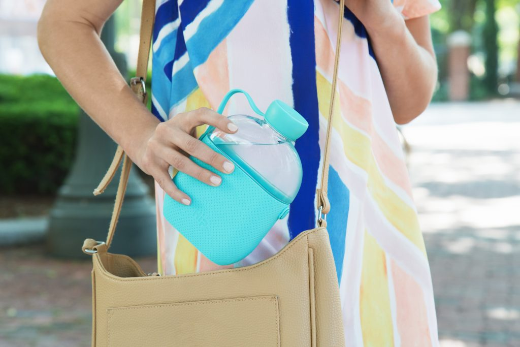 A woman is seen placing a teal HIP flask water bottle in her purse