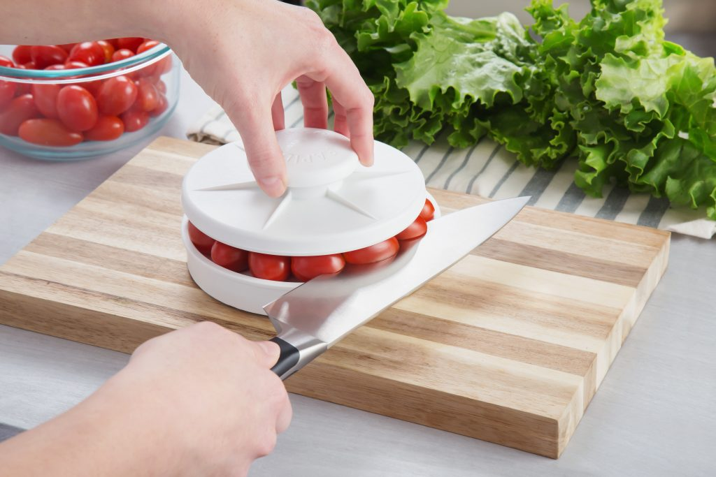 A person is seen slicing a tray of cherry tomatoes all at once with Rapid Slicer