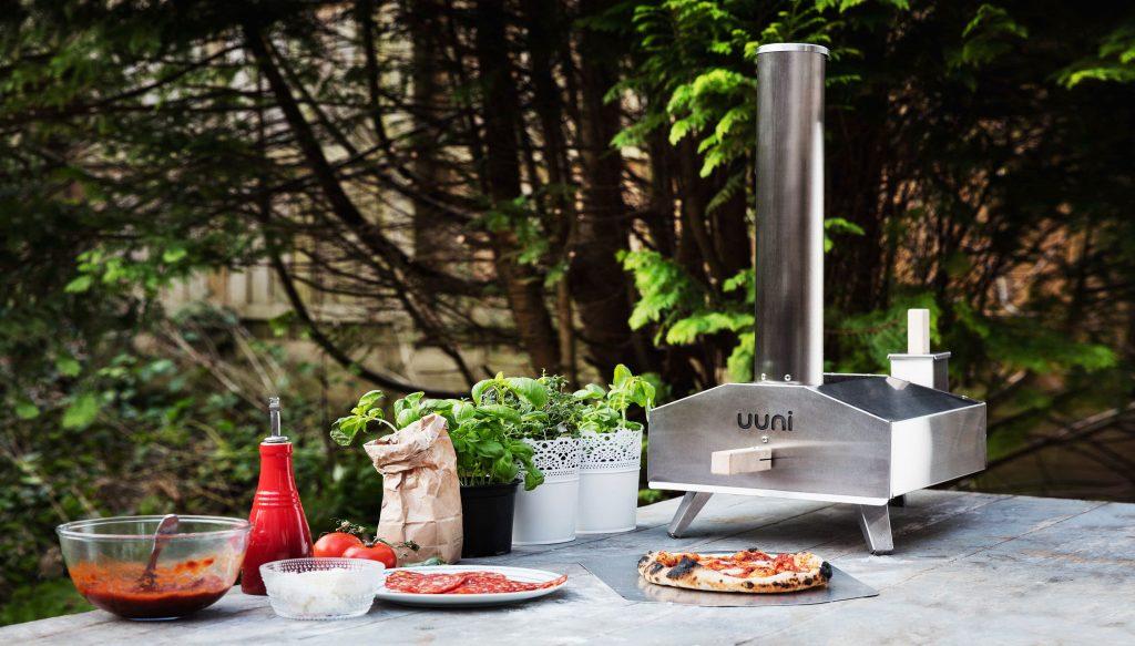 A blistered pepperoni pizza sits on a table with all the ingredients laid out next to the Uuni 3 wood fired pizza oven
